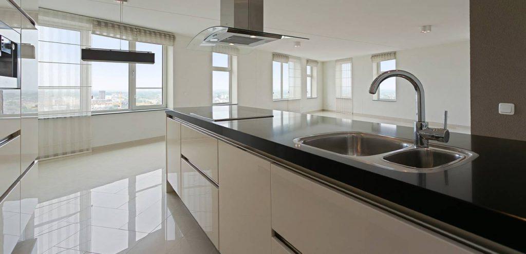 Moderne woonkamer van mooie huurwoning. Met zwarte tegels, een lederen bank en licht houten meubels. De huurwoning van een bestaande klant van Tenant Huurwoningen